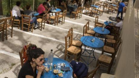 Gäste sitzen in einem Café im Stadtteil Monastiraki im Zentrum Athens.