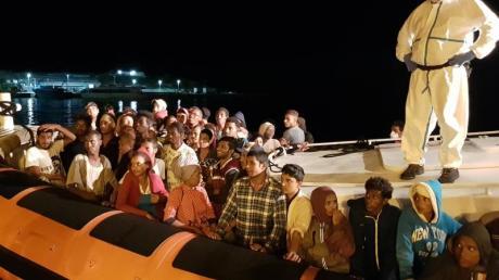 Flüchtlinge bereiten sich darauf vor, bei ihrer Ankunft im Hafen von Lampedusa aus einem Beiboot zu steigen (Archiv).