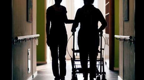 Eine Pflegerin (l) begleitet die Bewohnerin eines Altenheims beim Gang über den Flur.