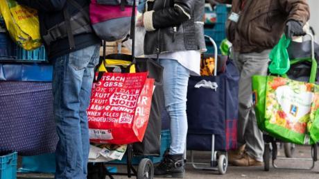 Gäste der Münchner Tafel stehen an der Ausgabestelle am Großmarkt.