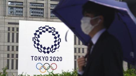 Ein Mann mit Mund-Nasen-Schutz geht im Regen an einem Banner der Olympischen Spiele Tokio 2020 vorbei.