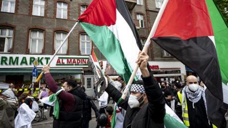 Teilnehmer einer Demonstration verschiedener palästinensischer Gruppen laufen mit Palästina-Flaggen durch Neukölln.