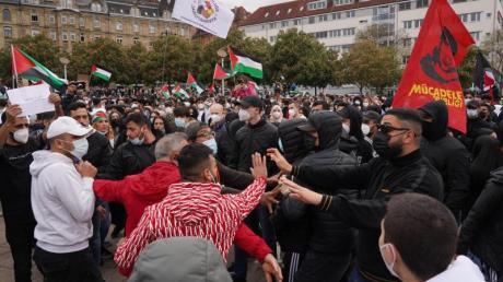 Teilnehmer einer pro-palästinensische Demonstration stehen auf dem Marienplatz in Stuttgart. Am Rande der Kundgebung kam es zu Rangeleien zwischen unterschiedlichen Gruppen und zwischen Demonstranten und der Polizei.