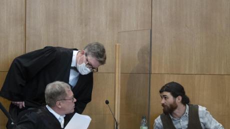 Der Angeklagte Franco A. spricht im Hochsicherheitssaal des Oberlandesgerichts mit seinen Verteidigern.