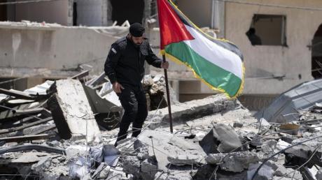 Ein Polizist der Hamas entfernt eine palästinensische Fahne von einem Trümmerhaufen eines Bahnhofsgebäudes, das bei Luftangriffen zerstört worden war.