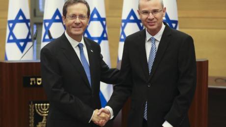 Izchak Herzog (l) gibt Knesset-Präsident Jariv Levin vor einer Sondersitzung die Hand. Israels Parlament hat den früheren Oppositionsführer zum Staatspräsidenten gewählt.