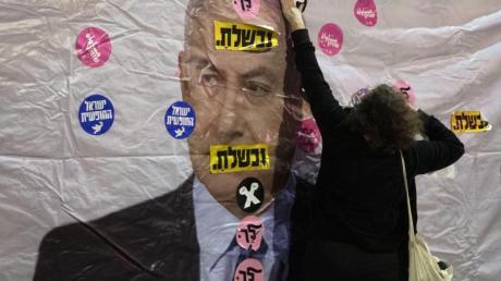 Ein Plakat mit dem Konterfei von Israels Premierminister Netanjahu wird mit Aufklebern überklebt.
