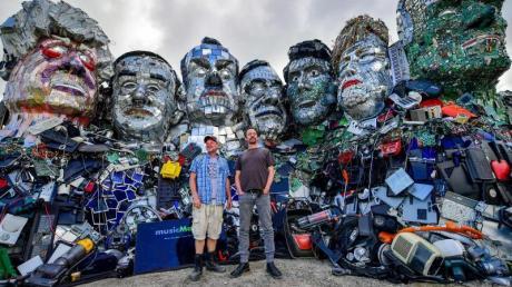 Die Künstler Alex Wreckage (l) und Joe Rush von der «Mutoid Waste Company» stehen vor dem G7-Gipfel in Cornwall vor ihrem Kunstwerk «Mount Trashmore» am Strand bei Gwithian. Eines der größten Themen beim G7-Gipfel soll der Klimaschutz sein.