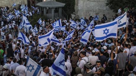 Menschen schwenken israelische Fahnen bei dem umstrittenen Flaggenmarsch in Jerusalem, der von rechtsgerichteten Nationalisten in Israel organisiert worden ist. Tausende Nationalisten zogen bei dem Marsch durch die Stadt.