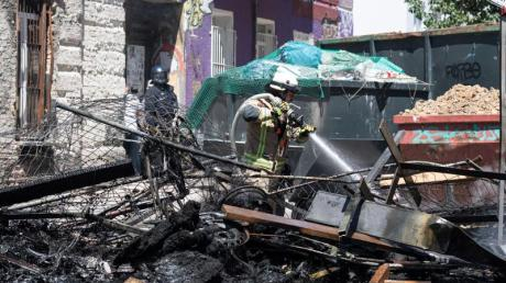 Ein Feuerwehrmann löscht eine brennende Barrikade in der Rigaer Straße in Berlin-Friedrichshain.