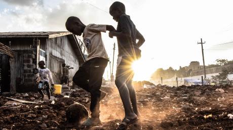 Zwei Kinder in Kenia spielen mit einem Ball. Für viele Heranwachsende war die Schule auch deshalb wichtig, weil sie dort eine Mahlzeit erhalten haben. Das fällt nun wegen Corona weg.