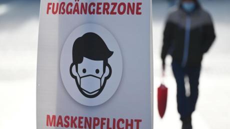Ein Schild weist auf die Maskenpflicht in der Fußgängerzone hin.