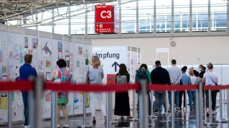 Menschen warten im Impfzentrum an der Messe München auf ihre Impfung.