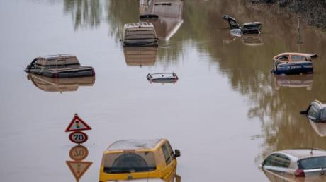 Autos stehen auf der überfluteten Bundesstraße 265 in Erftstadt im Wasser.