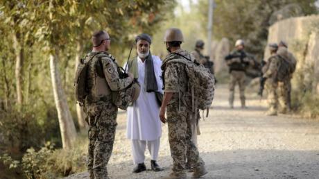 Ein Bundeswehrsoldat (l.) und ein Dolmetscher (r.) sprechen im August 2011 nahe Kundus mit einem Mann.