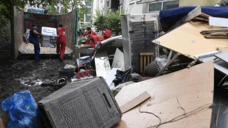 Helfer beseitigen in Opladen in Nordrhein-Westfalen die nach der Flutkatastrophe zurückgebliebenen Müllberge.
