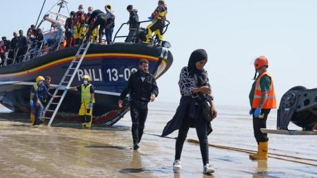 Eine Gruppe von Menschen, bei denen es sich vermutlich um Migranten handelt, geht von Bord des örtlichen Rettungsboots in Kent, nachdem sie nach einem Zwischenfall mit einem kleinen Boot im Ärmelkanal aufgegriffen wurde.
