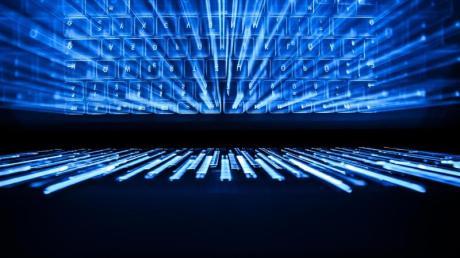 Die beleuchtete Tastatur eines Laptops spiegelt sich im Bildschirm.
