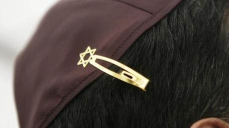 Ein Jude hat sich bei den Feierlichkeiten einer Grundsteinlegung für eine Synagoge seine Kopfbedeckung (Kippa) mit einer Davidstern-Klammer am Haar befestigt.