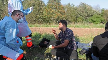 Sanitäter sprechen mit der Gruppe von Flüchtlingen an der polnisch-belarussischen Grenze.