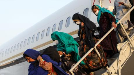 Mitglieder des US-Militärs helfen afghanischen Frauen auf dem Militärflughafen Sigonella in Italien aus dem Flugzeug.