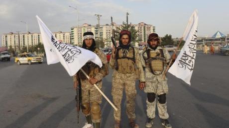 Kämpfer der Taliban stehen mit Flaggen auf einer Straße in der afghanischen Hauptstadt Kabul.