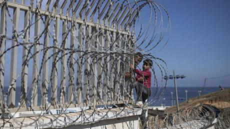 Auf dem Weg zur Grenze zwischen Marokko und Spanien hilft ein Mann einem Jungen über einen Stacheldrahtzaun in der marokkanischen Küstenstadt Fnideq.