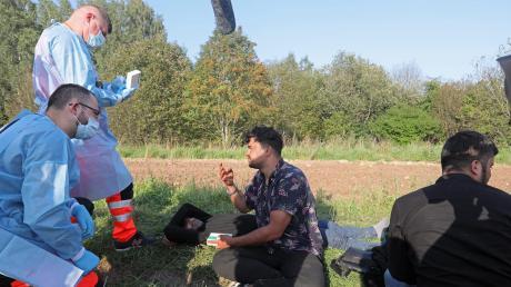 Rettungssanitäter sprechen mit einer Gruppe von 24 Flüchtlingen, die seit Tagen in der Nähe des Dorfes Usnarz Gorny im Grenzgebiet zu Belarus ausharren.