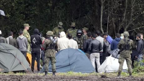 Migranten, die an der Grenze zu Belarus festsitzen, werden von polnischen Beamten umstellt.