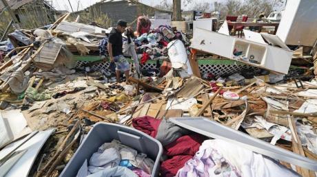 Jose Duran (l) hilft seiner Mutter Cruz Palma, die Überreste ihres Hauses nach dem Hurrikan Ida zu durchsuchen.