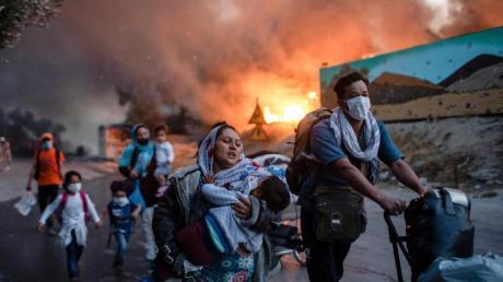 Migranten fliehen vor einem großen Feuer mit ihren Habseligkeiten aus dem Flüchtlingslager Moria.