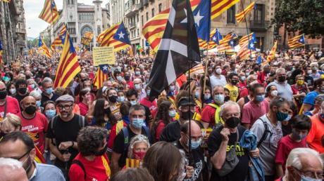 Demonstranten halten die katalanische Unabhängigkeitsfahne in die Höhe.