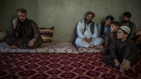 Afghanische Kinder und andere Taliban beobachten Matiullah Ruhani, den Sprecher der Taliban für Kundus, während er ein Telefonat führt.