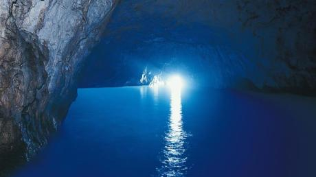 Durch einen kleinen Eingang fällt Licht in die berühmte Blaue Grotte von Capri. Es wird schnell ersichtlich, woher der Name der Meereshöhle kommt.