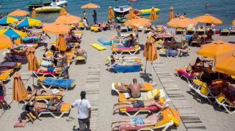 In Griechenland herrscht eine extreme Hitze. Einigen Touristen macht das nichts aus. Sie sonnen sich weiter. Foto: Santi Palacios/dpa