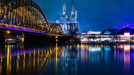 Die Hohenzollernbrücke und der Kölner Dom bei Nacht.