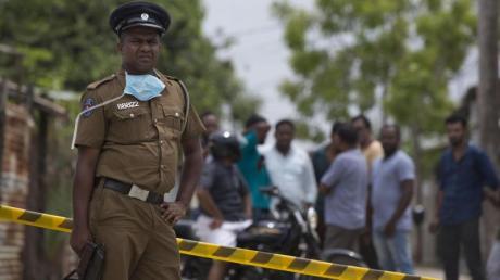 Ein Polizist bewacht in Sri Lanka einen Tatort. Das Auswärtige Amt hat die Lage in demLand neu bewertet.