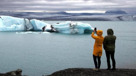 Touristen machen Fotos vom See und den darin schwimmenden Eisbergen. Die südisländische Lagune erfreut sich äußerster Beliebtheit.