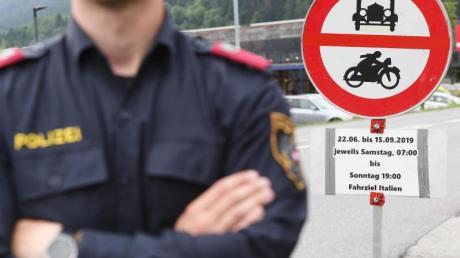 Ein Polizist steht vor einem Schild, das auf die Sperrung für den Verkehr mit Fahrziel Italien hinweist.