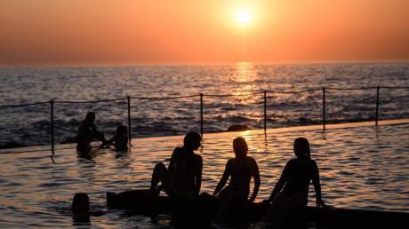 Schwimmer verfolgen den Sonnenaufgang am Bronte Beach Pool vom Ocean-Pool aus. Das Schwimmen und Baden in Meerwasser-Pools hat in Australien Tradition. Foto: James Gourley/AAP/dpa