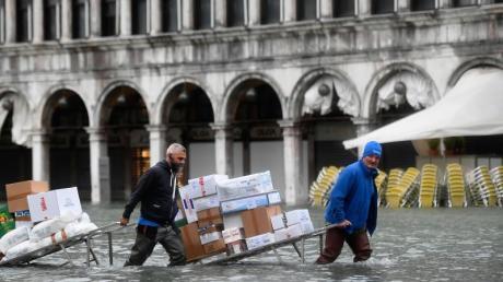 Männer waten mit Kartons und Lebensmitteln, die sie auf einer Trage transportieren, durch das Hochwasser auf einem überfluteten Platz.