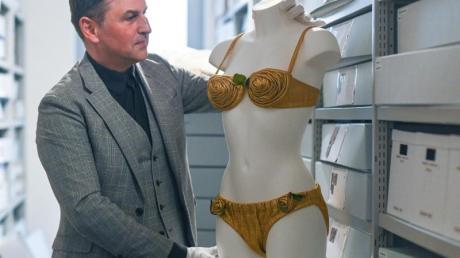 Reinhold Weinmann, Museumsdirektor des Bikini Art Museums, steht neben einem goldenen Bikini aus der Zeit um 1950 von Louis Réard.