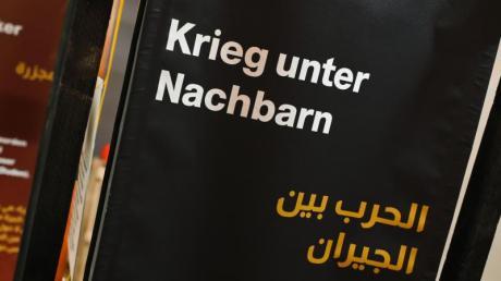 """Auf Bannern sind die Schriftzüge """"Massaker"""" und """"Krieg unter Nachbarn"""" zusammen mit arabischer Übersetzung zu lesen."""