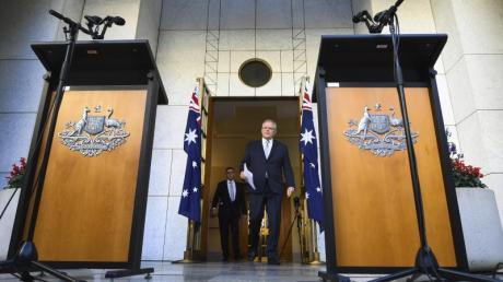 Scott Morrison (r), Premierminister von Australien trifft im Parlamentsgebäude ein: Im Australiens Regierung hat seinen Bürgern bis auf Weiteres jegliche Reisen ins Ausland untersagt.
