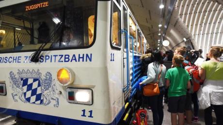 Touristen warten an der Bayerischen Zugspitzbahn.