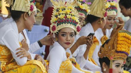 Balinesische Tänzerinnen und Tänzer in traditioneller Kleidung warten auf ihren Auftritt beim Kuningan-Fest in einem Hindu-Tempel.