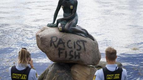 Polizeibeamte stehten an der Statue der kleinen Meerjungfrau, die von Unbekannten mit dem Schriftzug «Racist Fish» (Rassistischer Fisch) beschmiert wurde.