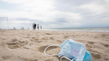 Ein gebrauchter Mundschutz mit Resten von Lippenstift liegt am Strand vor der Strandpromenade von Westerland auf Sylt.