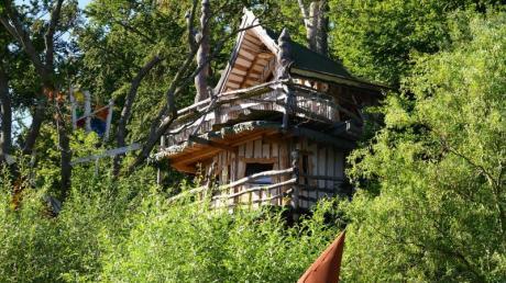 Das Romantikbaumhaus (l) ragt im Baumhaushotel Kriebelland zwischen den Bäumen hervor.