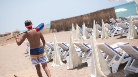 Ein Mann mit einem Besen geht an einem leeren Strand in Antalya entlang. Die Bundesregierung hat die Reisewarnung für die Türkei teilweise aufgehoben.